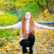 Redhead girl throwing leaves in autumn park — Stock Photo