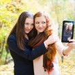Two girls taking self portrait in autumn park — Stock Photo