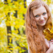 Royalty-Free Stock Photo: Redhead girl with yellow autumn leaves