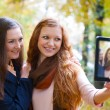 Two girls taking picture with digital tablet - Stock Photo