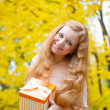 Redhead girl with present box in autumn park — Stock Photo