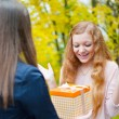 Beautiful girl accepting gift — Stock Photo #14045605