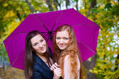 Two girls under umbrella in autumn park — Stock Photo