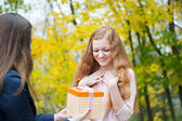 Young girl giving birthday present box — Stock Photo