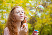 Young redhead girl blowing bubbles — Stock Photo