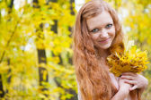 Redhead girl with yellow autumn leaves — Stock Photo