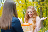 Beautiful girl accepting a gift — Stock Photo