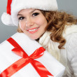 Beautiful young woman in Santa hat with present box — Stock Photo