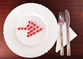 Red arrow from balls towards cutlery — Stock Photo