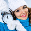 Beautiful young girl in winter clothes with alarm clock — Stock Photo