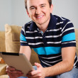 Stock Photo: Young man with digital tablet at home