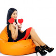 Beautiful young brunette sitting on couch with red Valentine hea — Stock Photo