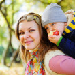 Young mother with her little son in autumn park — Stock Photo