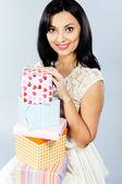 Muito jovem morena sentando com caixas coloridas de presentes — Foto Stock