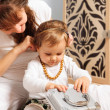 Mother and baby daughter playing with jewelry - Stock Photo