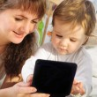 Stock Photo: Mother and baby son playing with digital tablet