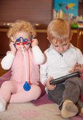 Irmão com tablet digital, irmã com kit médico de brinquedo — Foto Stock
