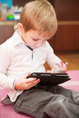 Cute boy playing with tablet — Stock Photo