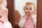 Cute baby applying cream on her cheeks — Stock Photo