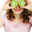Young woman holding kiwi fruit for her eyes — Stock Photo #19413391