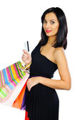 Beautiful brunette with credit card and shopping bags isolated o — Stock Photo