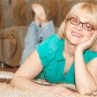 Blonde smiling woman lying on floor at home — Stock Photo