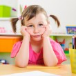 Upset little girl sitting at desk — Foto de Stock