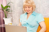 Happy mature woman with laptop at home — Stock Photo