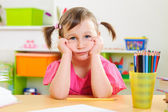 Upset little girl sitting at desk — Stock Photo
