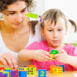 Stock Photo: Young mother and little daughter playing with toy blocks