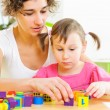 Young mother and little daughter playing with toy blocks — Stock Photo