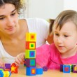 Young mother and little daughter playing with toy blocks — Stock Photo #19498561
