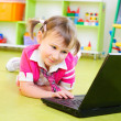 Cute little girl with laptop on floor — Stock Photo