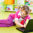 Royalty-Free Stock Photo: Cute little girl in glasses with laptop on floor