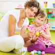 Stock Photo: Young mother and daughter painting Easter eggs