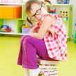 Cute little girl in eyeglasses sitting on stack of books — Stock Photo