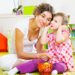 Young mother and little daughter painting Easter eggs - Stock Photo