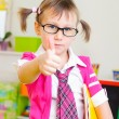 Cute little girl in glasses showing thumb up — Stock Photo