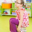 Tired little girl sitting on stack of books — Foto Stock