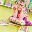 Funny little girl with books on floor — Stockfoto