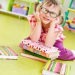 rolig liten flicka med böcker på golvet — Stockfoto