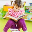 Cute little girl reading book sitting on floor — Stok fotoğraf