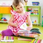 Little girl reading book on floor — Stock Photo