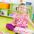 Funny little girl with books on floor — Stok fotoğraf