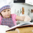 Little girl preparing cookies with cookbook — Stock Photo