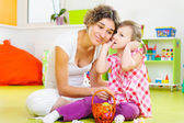 Young mother and little daughter painting Easter eggs — ストック写真