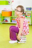 Moe meisje, zittend op stapel boeken — Stockfoto