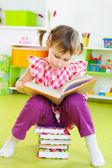 Cute little girl reading book sitting on floor — Foto de Stock