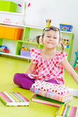 Funny little girl with books on floor — Stock Photo