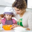Young mother with little daughter preparing cookies — Stock Photo